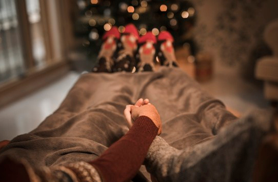 man-and-woman-holding-hands-and-lying-near-christmas-tree_23-2147987518